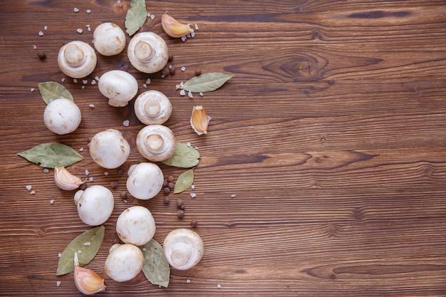 キノコのキノコと木製の背景の食材。テキスト用のスペース、メニュー用の背景