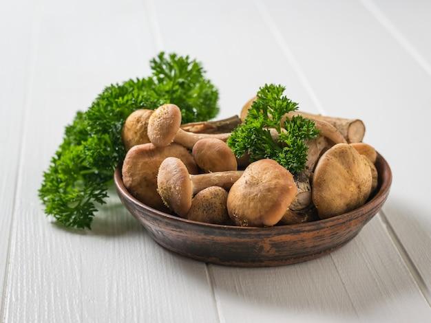 きのこ木製のテーブルの上にパセリと粘土のボウルにきのこ。テーブルの上の森のキノコ。ベジタリアン料理。
