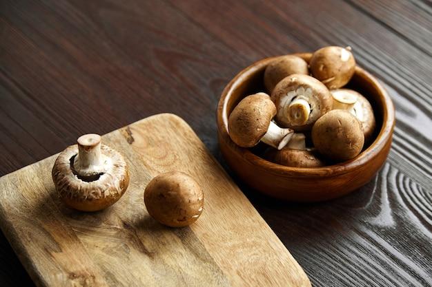 Грибы на разделочной доске много свежих коричневых шампиньонов в миске на деревянном столе