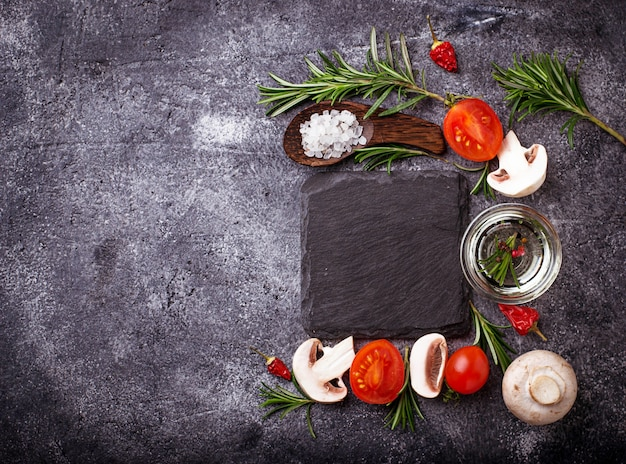 Mushrooms, tomatoes, rosemary, salt and oil. food background. top view. space for text