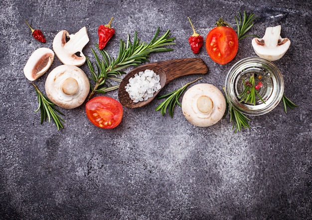 Mushrooms, tomatoes, rosemary, salt and oil. food background. top view