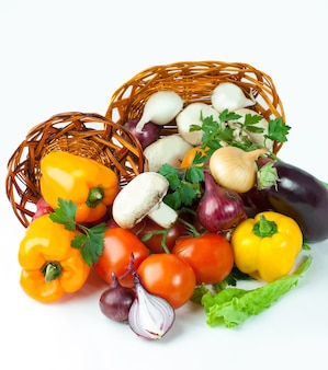 Mushrooms and a variety of fresh vegetables in a wicker basket.isolated on a white background.photo with copy space