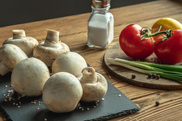 Mushrooms, vegetables and spices on a wooden table. concept of ingredients for cooking a delicious food.