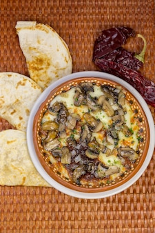 Mushrooms with cheese, some quesadillas and chili on a wooden