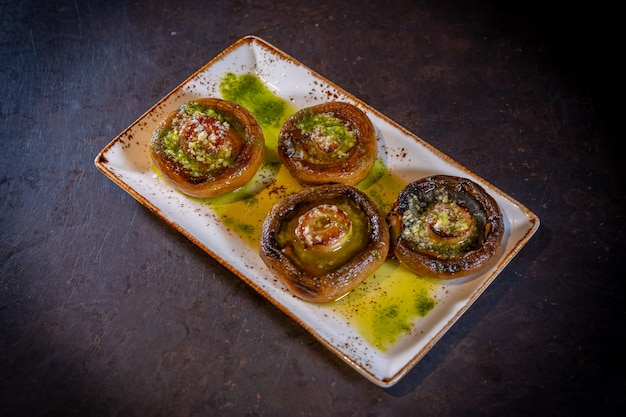 Mushrooms with olive oil and garlic on a black background, on a white plate