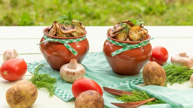 Грибы с картошкой и мясом, приготовленные в глиняном горшочке в каменной печи. в природе.