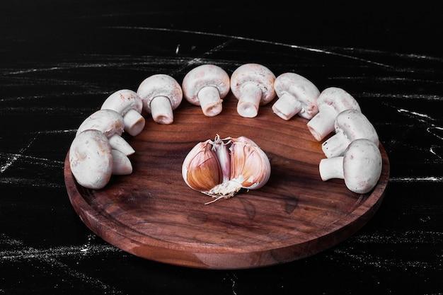 Funghi in un vassoio di legno con uno spicchio d'aglio