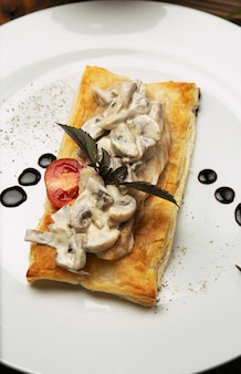 Mushtoom sauteed, chicken stroganoff on a piece of bread. antipasta in a decorated white plate with cutlery on wooden table