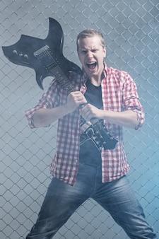 音楽。フェンスの壁にギターを持つ積極的なミュージシャン