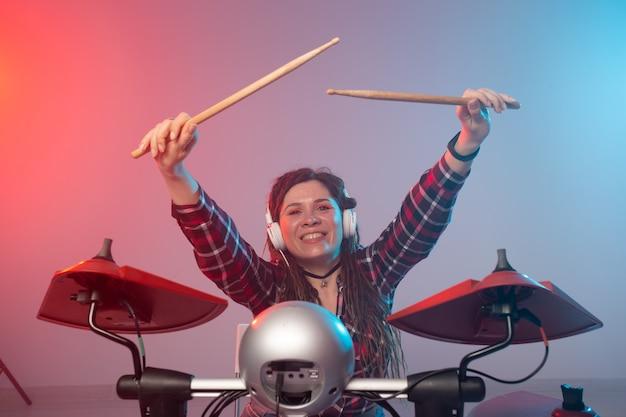 음악과 취미 개념-전자 드럼 세트를 연주하는 여자 드러머