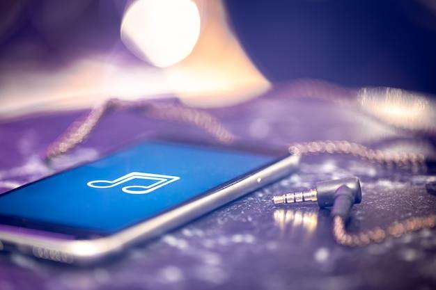 電話とヘッドフォンの音楽リスニングアイコンと音楽の背景。