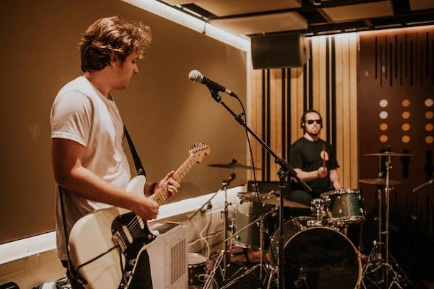 Гитарист музыкальной группы выполняет повторение в студии звукозаписи