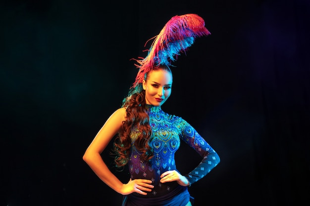 Music. beautiful young woman in carnival, stylish masquerade costume with feathers on black background in neon light. copyspace for ad. holidays celebration, dancing, fashion. festive time, party.