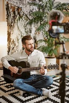 Музыкальный блогер играет на гитаре и поет, записывая новое видео для своих подписчиков.