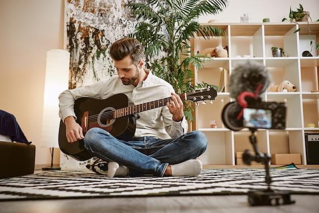 Музыкальный блогер сидит на полу и держит гитару во время записи нового видео для своего видеоблога. Premium Фотографии