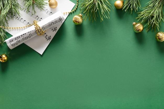 Музыкальная новогодняя композиция для колядок и песен, украшенная золотыми шарами на зеленом