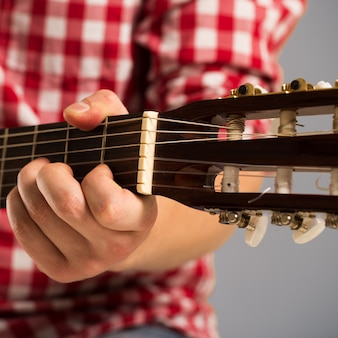 Music, close-up. musician holding a wooden guitar