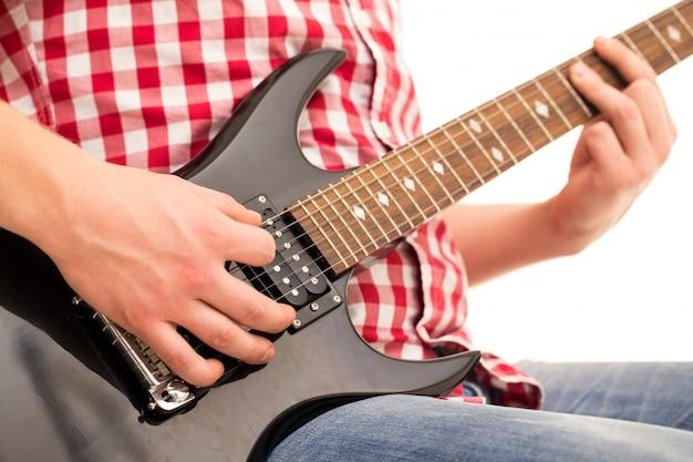 音楽、クローズアップ。電気ギターを抱えて若いミュージシャン