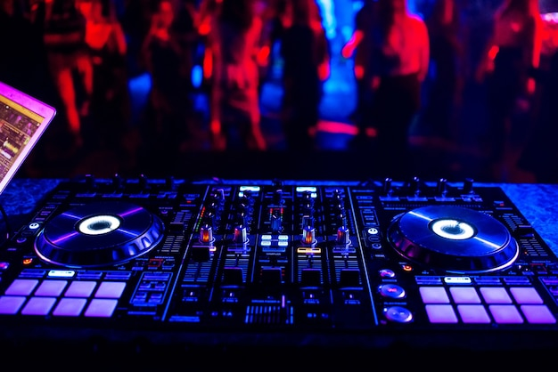 ダンスの人々のぼやけたシルエットを背景にパーティーでナイトクラブで音楽コントローラーdjミキサー