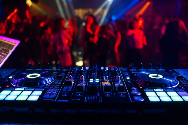 Music controller dj mixer in a nightclub at a party