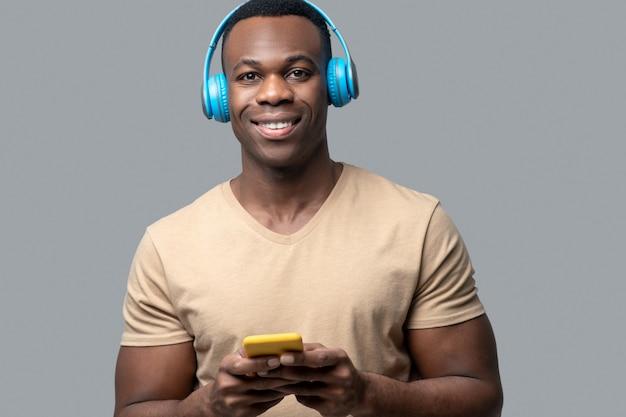 音楽。音楽を聴いているヘッドフォンで浅黒い肌の若い男