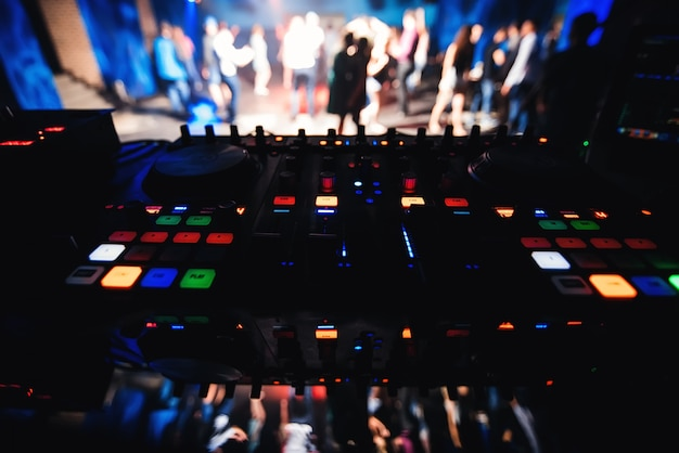 Music dj desk with blurred dance floor with dancing people in night club