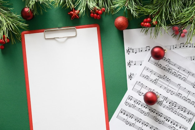 Music empty frame for christmas carols and sings decorated red balls on green background