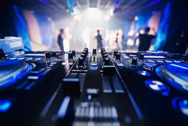 Music equipment dj in nightclub closeup with blurred dancing people