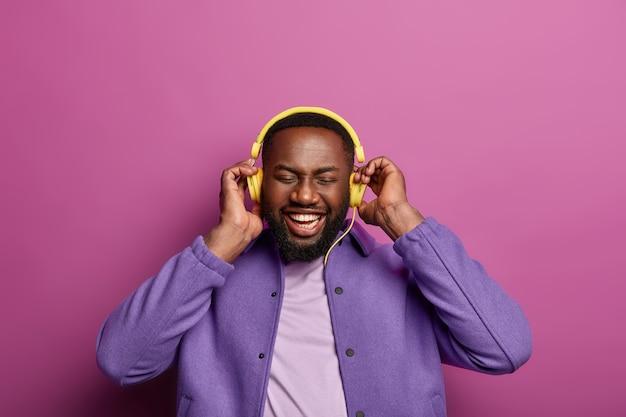 음악 팬 개념. 짙은 털로 웃는 흑인 남자, 음악 액세서리 장치 사용, 헤드폰에서 완벽한 사운드 즐기기, 넓은 미소, 하얀 치아