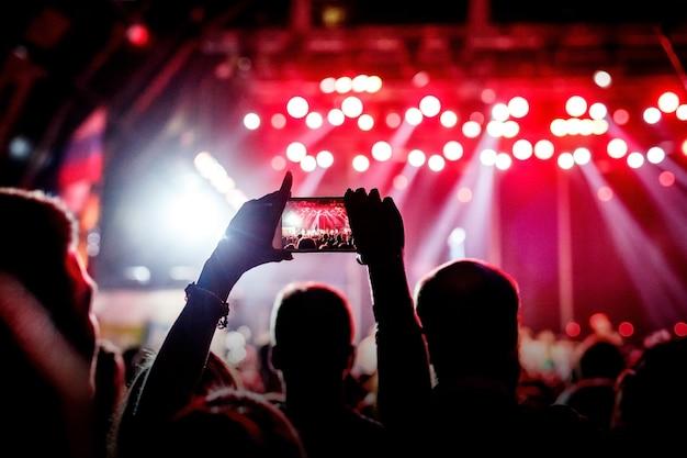 음악 팬들은 스마트 폰에서 콘서트 무대 사진을 찍습니다