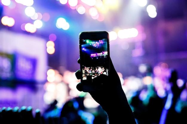 음악 팬들은 스마트 폰에서 콘서트 무대 사진을 찍습니다.