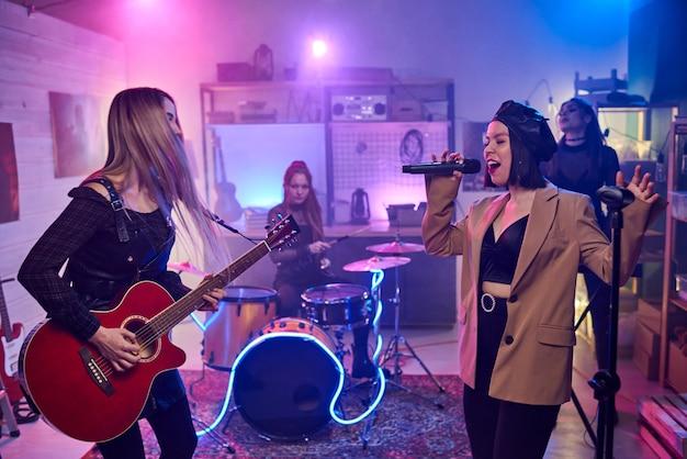 Музыкальный женский коллектив играет на музыкальных инструментах и выступает в ночном клубе