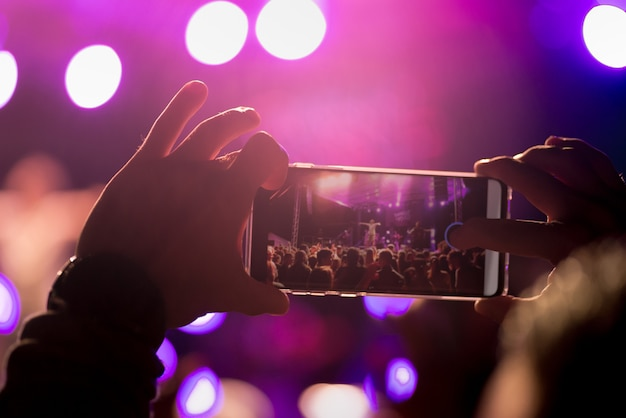 At a music festival, a man records his concert on his smartphone.