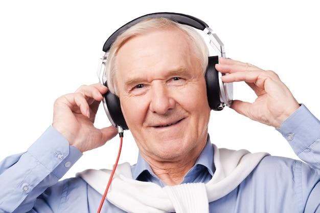모든 연령대를 위한 음악. 헤드폰을 끼고 흰색 배경에 서서 음악을 듣고 웃고 있는 노인 초상화