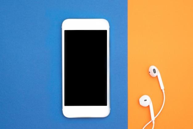 Музыка, гаджеты, меломан. белый смартфон и наушники на оранжевом и синем фоне с наушниками. вид сверху. плоская планировка, вид сверху.