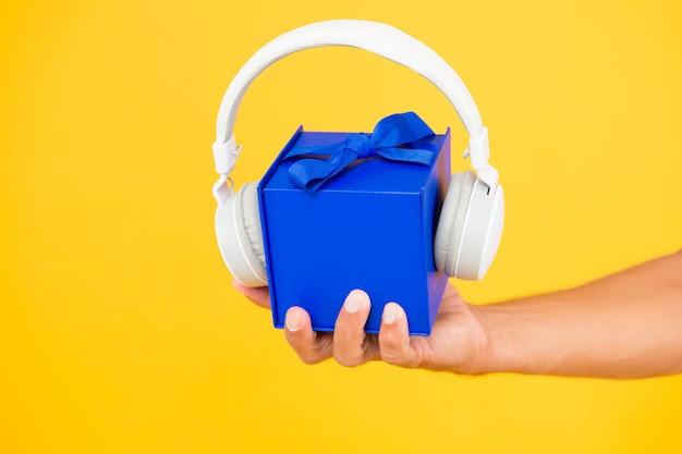 音楽ギフト部門。ヘッドフォン付きギフトボックス。男性の手は現在の黄色の背景を保持します。最新のヘッドセット。中には何がありますか。オーディオアクセサリーの販売。クリスマス音楽の贈り物。ミュージカルプレゼント。便利な配達。