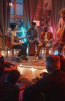 그들의 앞에 앉아 있는 팬과 함께 그들의 공연의 시작에 대해 논의하는 남성의 음악 그룹