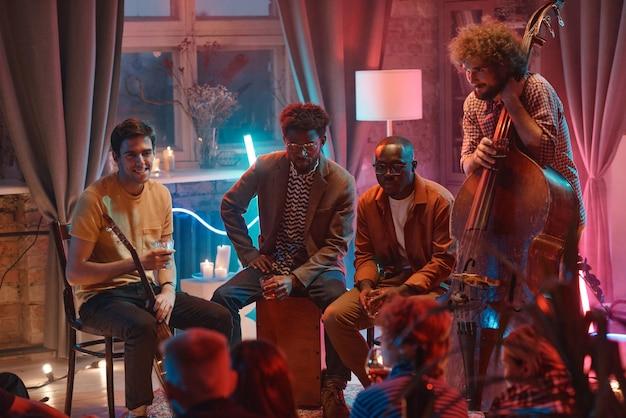 클럽에서 공연하는 동안 앉아서 팬들과 이야기하는 젊은 남성의 음악 그룹