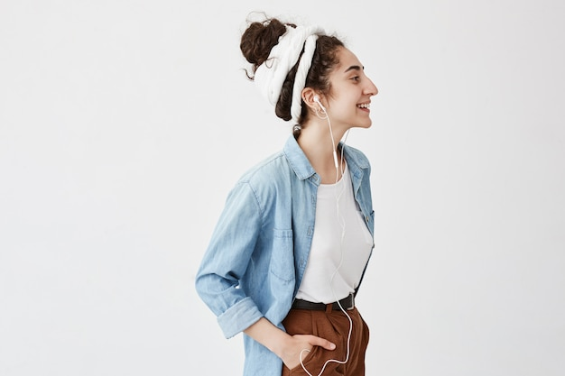 Music, happiness and technology. lovely stylish girl with hairbun, holds hand in pocket of brown trousers, listens to music on cell phone, poses against white wall with copy space for advertisment