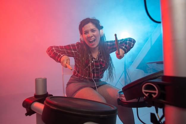 음악 취미와 사람들의 개념 헤드폰을 끼고 섹시한 여성 갈색 머리가 전자 드럼 키트에서 재생됩니다.