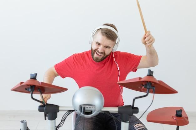 音楽、趣味、人々のコンセプト-電子ドラムを演奏する若い男性ドラマー。