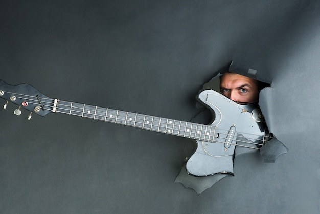 음악 악기. 남성의 얼굴은 종이를 통해 보입니다. 찢어진 검은 종이를 통해 일렉트릭 기타입니다. 전자 기타와 함께 종이 벽의 구멍에서 나오는 남자. 상점 악기 광고를 위한 공간 복사