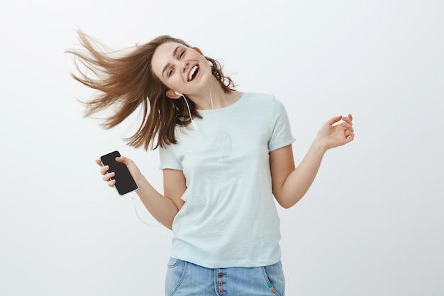音楽は素晴らしい感情を後押しします。灰色の壁にポーズをとってスマートフォンを保持しているイヤホンで音楽を聞いて喜んで髪を振ってジャンプして笑顔から魅力的な喜びと感情的な女性の肖像画