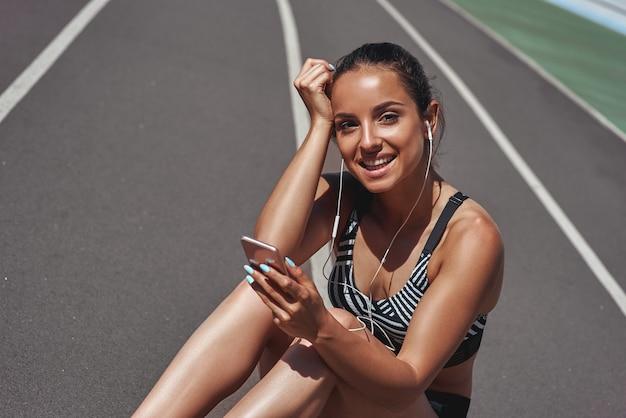 Музыка - это мой побег спортсмен на трассе стадиона женщина летняя фитнес-тренировка бег трусцой