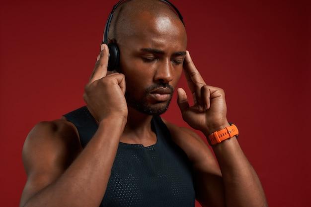 Музыка - моя мотивация. портрет красивого афроамериканца в наушниках с закрытыми глазами