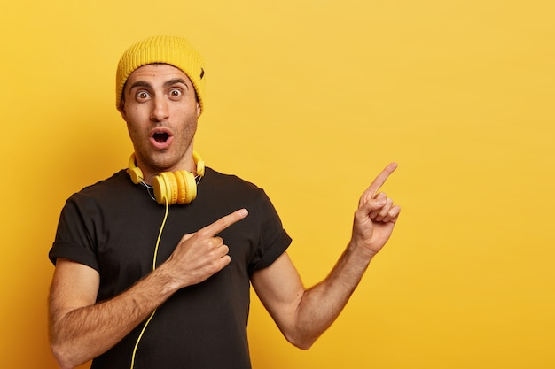 Music is part of technology. surprised caucasian man wears headphones, yellow headgear and black t shirt