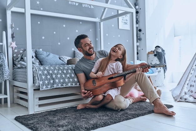 Music is so much fun. young father teaching his little daughter to play guitar and smiling