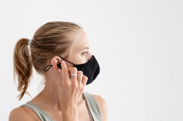 音楽、孤立、そして余暇。ワイヤレスイヤフォンを保持している保護マスクの若い女性