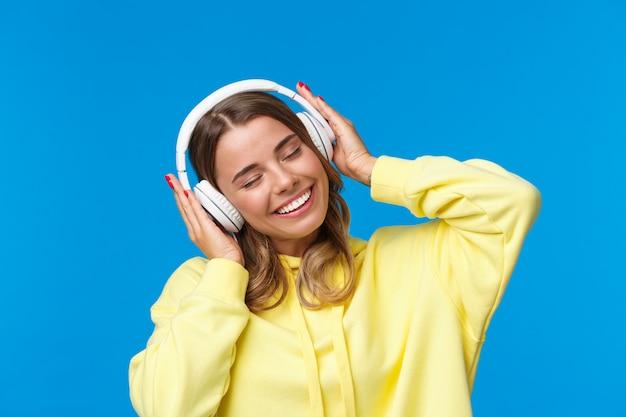 Музыка, образ жизни и молодежная концепция портрет крупным планом радостной милой молодой блондинки, слушающей любимую песню в наушниках, вибрирующей, улыбающейся в восторге,