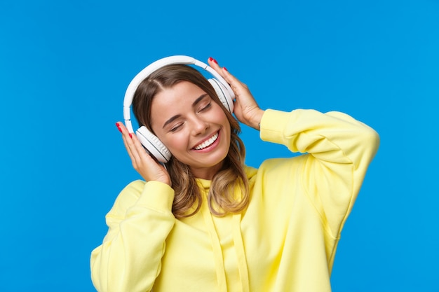 Music, lifestyle and youth concept close-up portrait of joyful cute young blond girl listening to favorite song in headphones, vibing, smiling delighted,